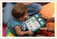 A toddler holds a language learning device